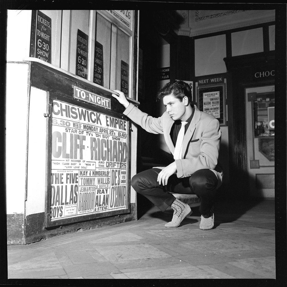 Halfway to Paradise: The Birth of British Rock - Cliff Richard in front of the poster for his first concert as Top of The Bill. Photograph by Harry Hammond