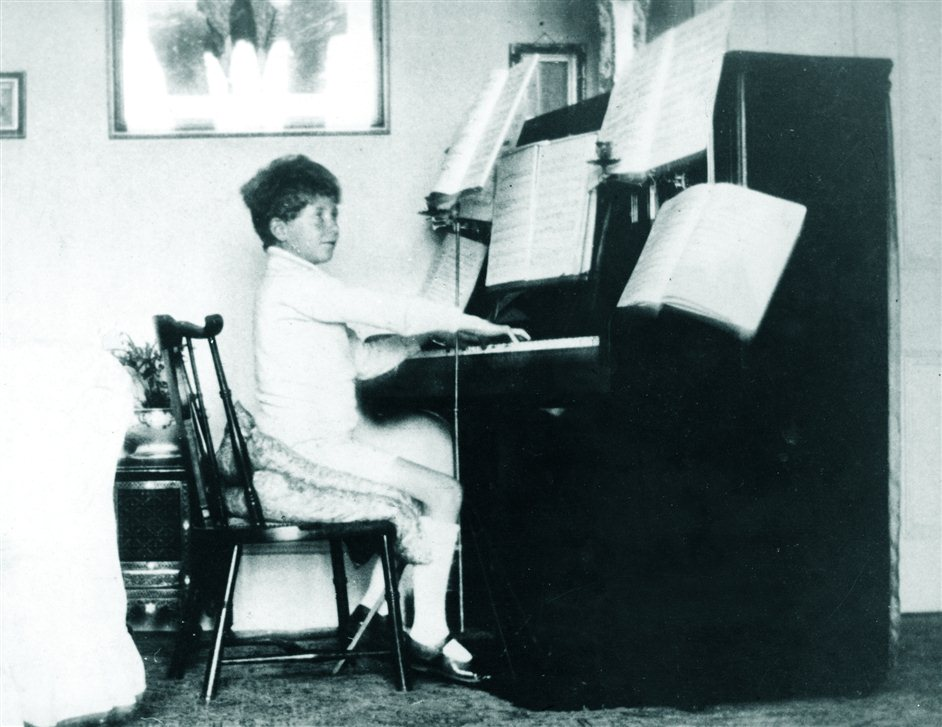 Britten's War Requiem - Britten1921 - Playing piano at home. Image courtesy of www.britten100.org.