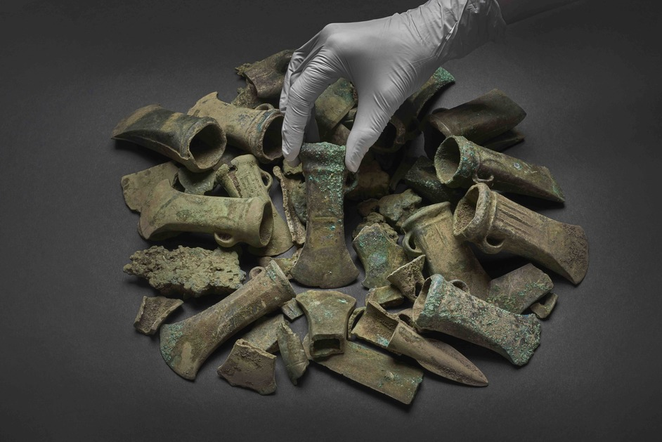 Havering Hoard: A Bronze Age Mystery - A Bronze Age axe head surrounded by a selection of objects from the Havering Hoard (c) Museum of London